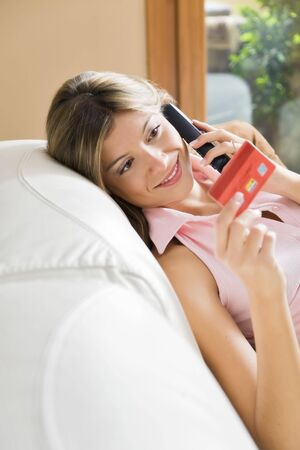 Young woman relaxing at home on the phone with credit card Stock Photo - 4313608