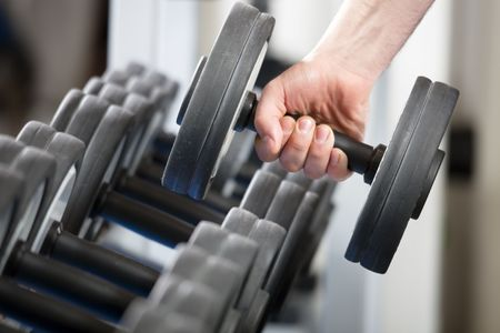 weight training: close up of man holding weight in gym