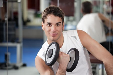 portrait of young man doing weightlifting in gym Stock Photo