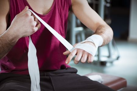 boxing tape: cropped view of boxer wrapping his hands in gym. Copy space