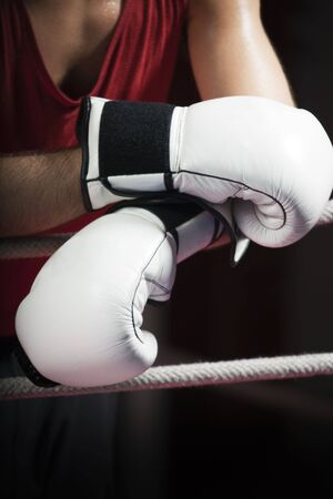 combative sport: cropped view of boxer leaning on ropes. Copy space