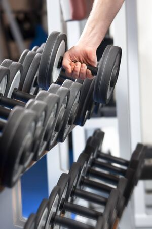 close up of man holding weight in gym photo