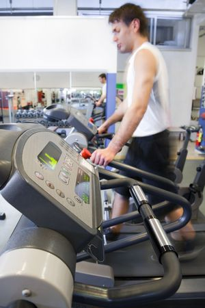portrait of young man running on treadmill in gym. Motion blur Archivio Fotografico