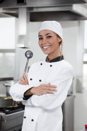 portrait of female chef looking at camera in kitchen photo