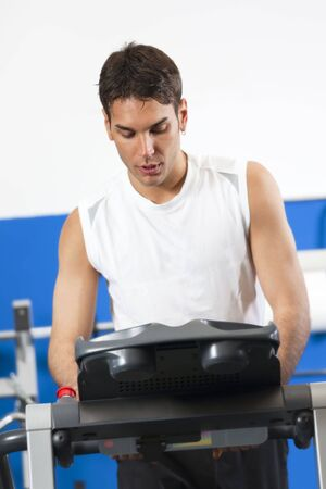 portrait of young man running on treadmill in gym Archivio Fotografico