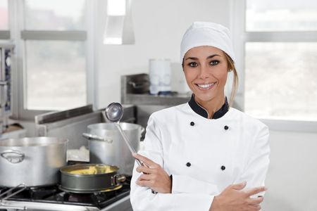 working attire: portrait of female chef looking at camera in kitchen Stock Photo
