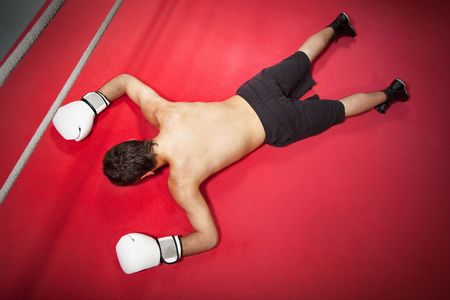 combative: Young adult man knocked down. Copy space Stock Photo