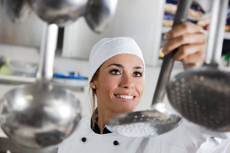 mid adult female chef taking kitchen utensil Stock Photo - 4427403