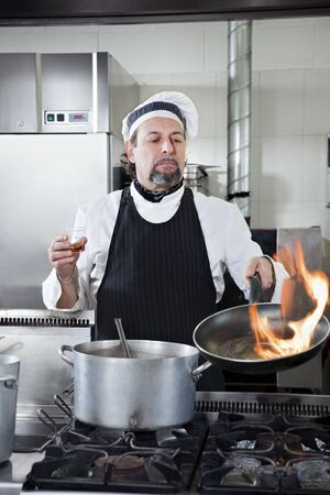 mature chef holding pan and doing flamb� photo