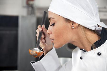 female chef tasting tomato sauce. Copy space
