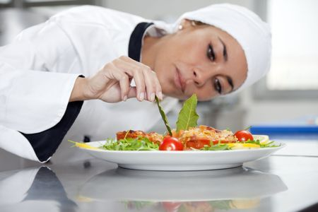 preparing: mid adult female chef in kitchen decorating dish