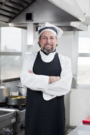 portrait of confident chef looking at camera in kitchen photo