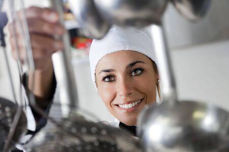mid adult female: mid adult female chef taking kitchen utensil