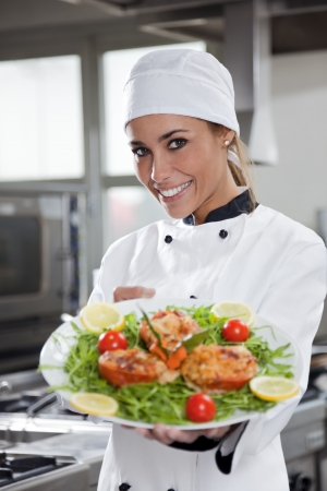 culinary: portrait of mid adult female chef in kitchen presenting dish