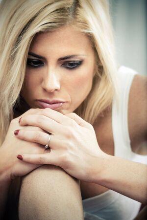knees bent: triste donna seduta sul divano con le ginocchia piegate
