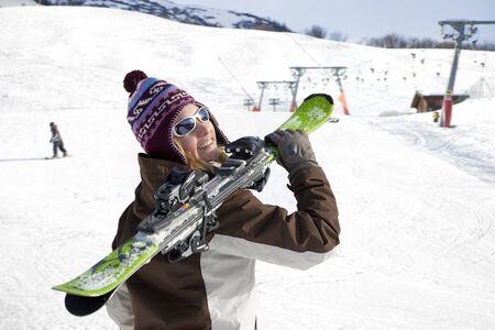 skieer: jonge vrouw uitvoeren ski's en kijken naar de camera. Kopieer de ruimte