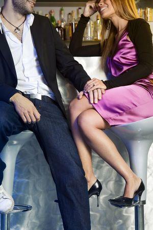 seducing: giovane coppia seduta su barra e sgabelli per mano Archivio Fotografico