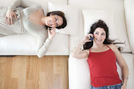 Two young women lying down on couch and talking on the phone. Copy space Stock Photo - 4523714
