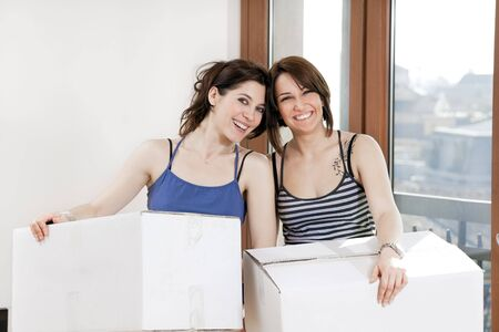 two young women holding cardboard boxes and looking at camera Stock Photo - 4523709