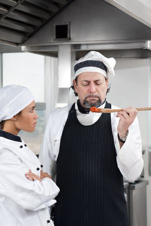 mature chef holding wooden spool and tasting tomato sauce.  photo