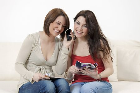 two young women talking on the phone at home photo