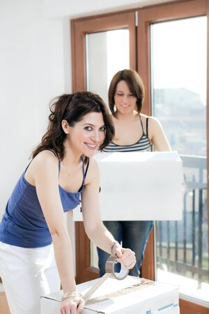 two young women packing and holding cardboard boxes Stock Photo - 4523716