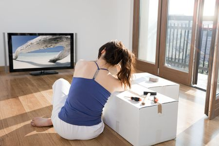 young woman in new house leaning on cardboard box and watching television photo