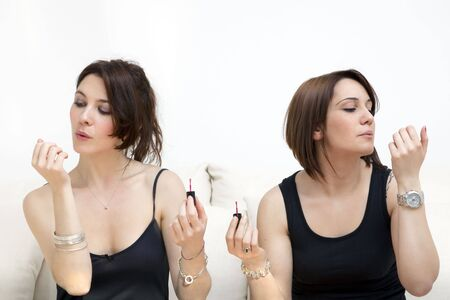 two young women blowing on nail varnish Stock Photo - 4553017