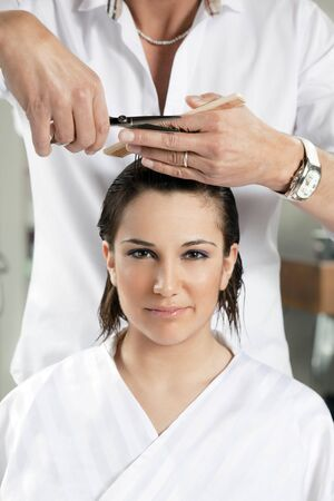 portrait of young woman having her hair being cut photo