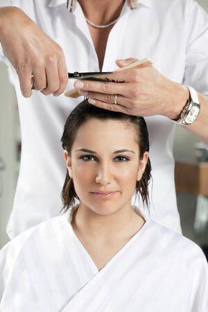 estilista: retrato de joven mujer que se corte el cabello Foto de archivo