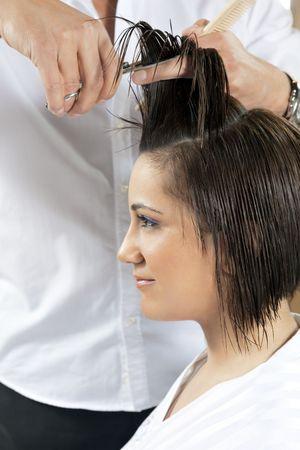 tijeras cortando: retrato de joven mujer que se corte el cabello Foto de archivo