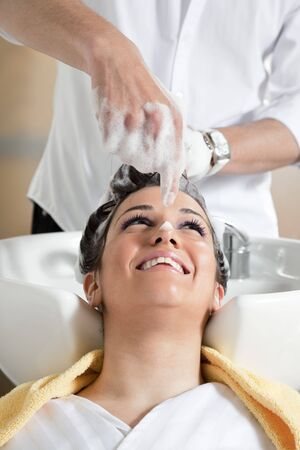 woman washing hair: portrait of young woman in hair salon playing with soap Stock Photo
