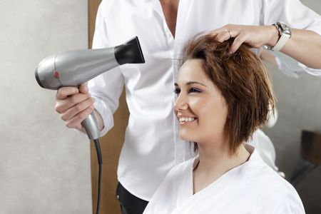 cropped view of hairstylist drying woman�s hair. Side view