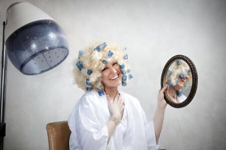 coiffeur: bizarre woman doing permanent wave and looking at camera. Copy space