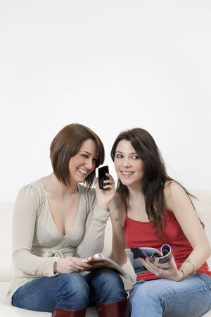 mobilephones: two young women talking on the phone at home