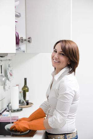 side view of young woman in kitchen doing housekeeping photo