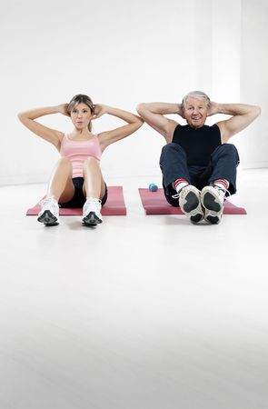 young woman and senior man doing abs in gym photo