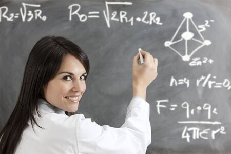 portrait of mid adult woman writing chemical formula on blackboard photo