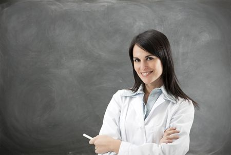teacher: portrait of mid adult teacher with arms folded against blank blackboard. Copy space