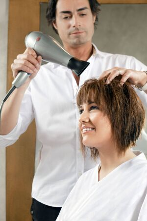mid adult hairstylist drying woman hair. Side view Stock Photo - 4632708