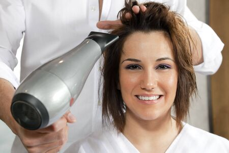 cropped view of hairstylist drying woman hair. Front view photo