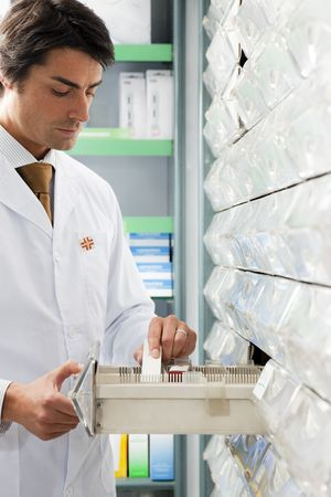 pharmacist taking medicine from drawer. Copy space photo