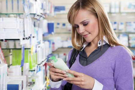 Portrait of blonde woman reading label of shampoo in pharmacy. Copy space photo