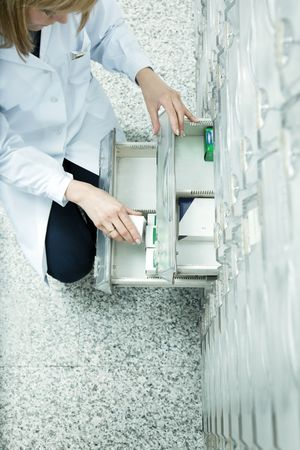 medicine cabinet: high angle view of pharmacist taking medicine from drawer. Copy space