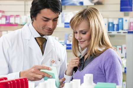 pharmacist holding medicine and talking to customer  photo