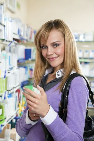 Portrait of blonde woman choosing shampoo in pharmacy. Stock Photo - 4646764