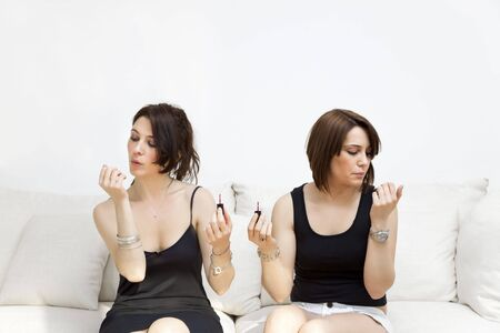 two young women blowing on nail varnish photo