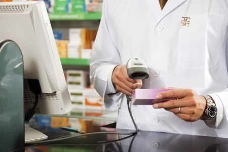 pharmacy equipment: cropped view of pharmacist scanning medicine with barcode reader