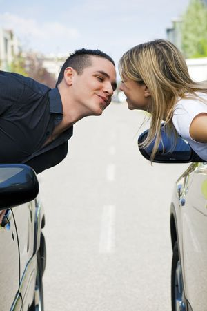 couple leaning out of car windows and kissing. Copy space photo