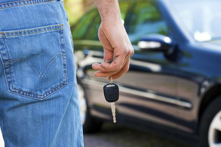 parked: close up of man holding keys to new car. Copy space